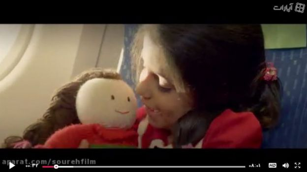 Girl with doll sitting in plane seat