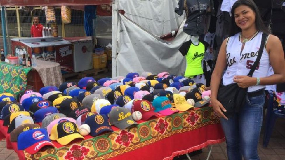 Un puesto de gorras y camisas de béisbol