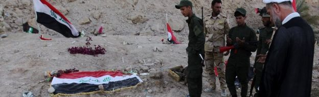 Iraqi Shia fighters examine a burial site thought to hold victims of the Camp Speicher massacre.