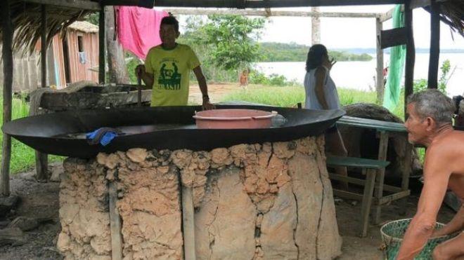 Três indígenas que moram próximo à estrada se reúnem ao redor de um fogão ao ar livre