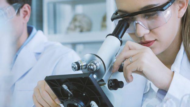 Muchacha en el microscopio