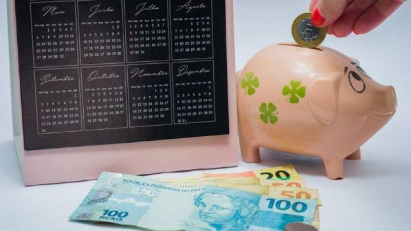 pessoa deposita dinheiro num cofrinho