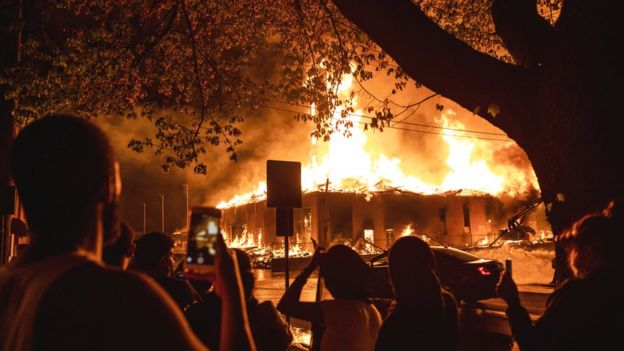 People look on as a construction site burns in a large fire near the Third Police Precinct