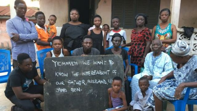 Martin Kyere with members of the family of Peter Mensah who was among the victims. His wife, dressed in black is holding the board at far right. Centre is Peter's son Isaac (grey shirt – aged 26), daughter Lauretta (white vest – aged 20) and Clement (black t-shirt, 21)
