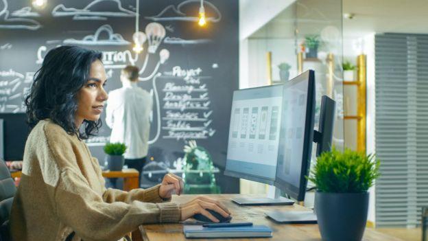 Una mujer con un sweater en una oficina y un hombre en el fondo con una camisa.