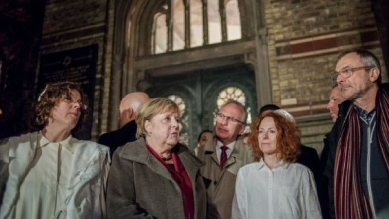 German Chancellor Angela Merkel (C) talks to Rabbi Gesa Ederberg (L) and other members of the Jewish community at a vigil outside the New Synagogue in Berlin