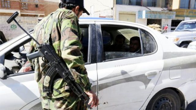 A Houthi rebel with a big gun standing outside the window of a car