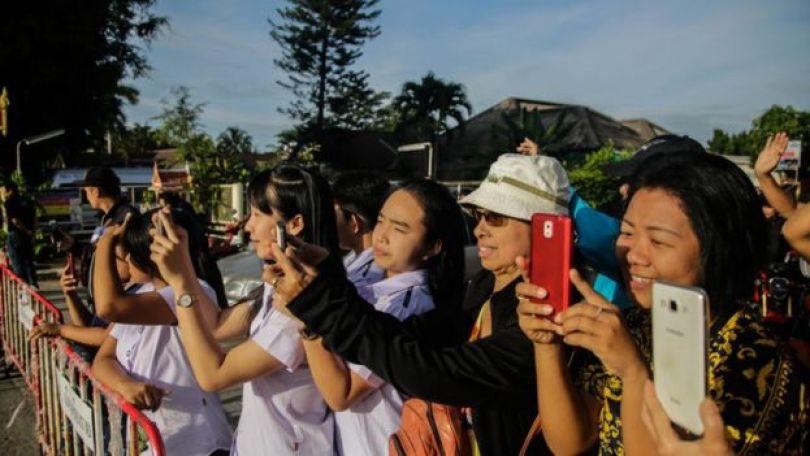 Mulheres tiram fotos com celulares ao lado de cerca que protege acampamento perto da caverna