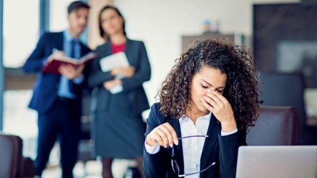 Una mujer se toca la cara en señal de estrés.