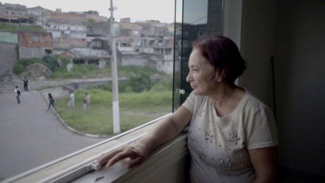 Empregada doméstica Merlene de Lima olha sua vizinhança pela janela de sua casa