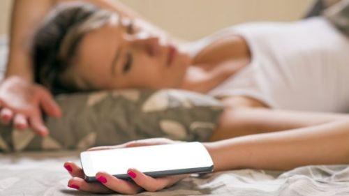 cep telefonuyla uyuyan kadın