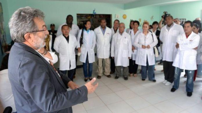 Alguns médicos participantes do Mais Médicos fazem roda enquanto escutam um homem engravatado falar