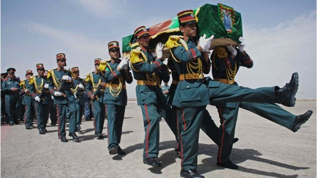 An Afghan honoree guard carries the coffin of a policeman