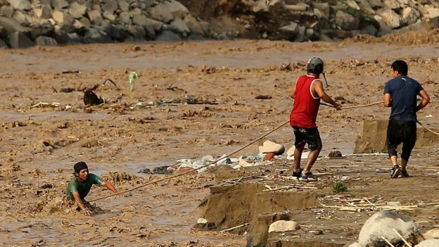 Joven cruzando el río Rimac en el distrito de Lima, Perú.