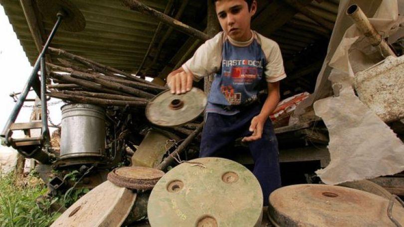 Um garoto segura minas terrestres desativadas na Croácia
