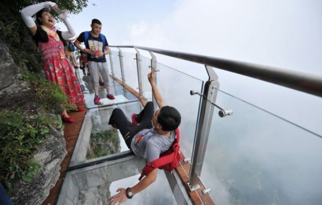 People take photos on the glass walkway on Tianmen Mountain (1 Aug 2016)