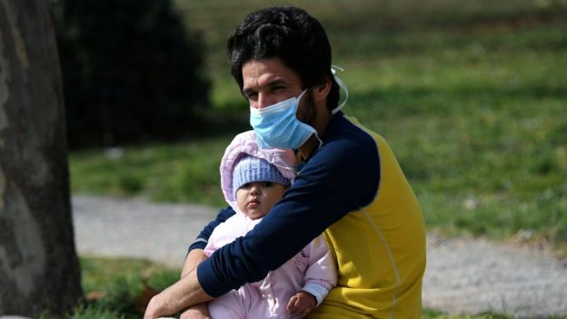 A man holds a baby outside the AHEPA hospital, where the first confirmed coronavirus case is being treated, in Thessaloniki, Greece,