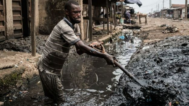 A man removes sludge from a ditch to improve the drainage system in the Mosafejo area of Lagos on February 12, 2019