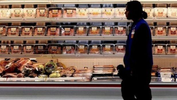 Woman walks past chicken in a US shop