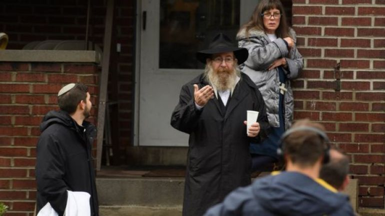 Un hombre judío conversa con periodistas en el porche de una casa.