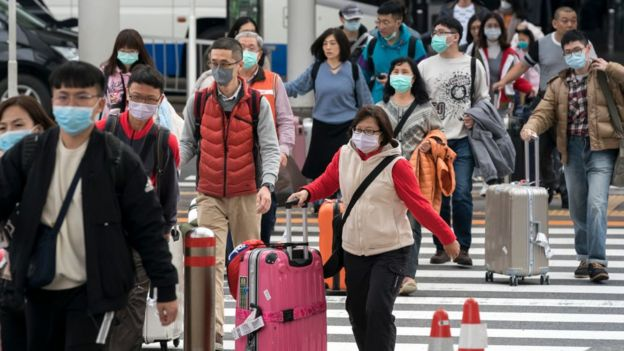 A group of Chinese tourists walks outside the arrival lobby at Narita airport on January 24, 2020 in Narita, Japan.