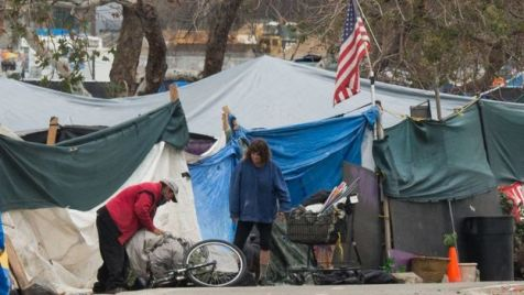 Homem e mulher consertando bicicleta em acampamento