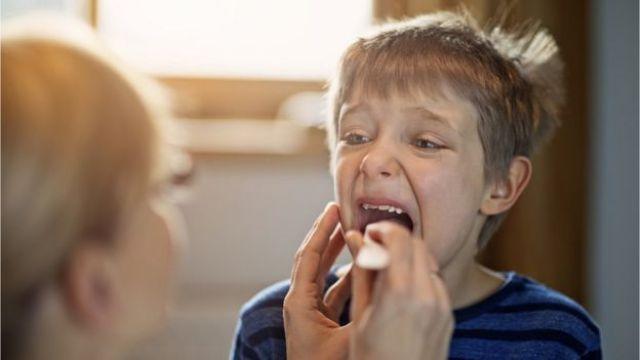 Menino abrindo a boca para ser examinado por médica