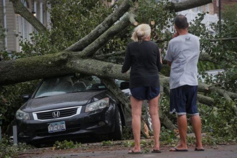 Les gens regardent un arbre tombé sur une voiture à la suite de la tempête tropicale Isaias dans la région de Rockaway dans le Queens à New York, États-Unis, le 4 août 2020.