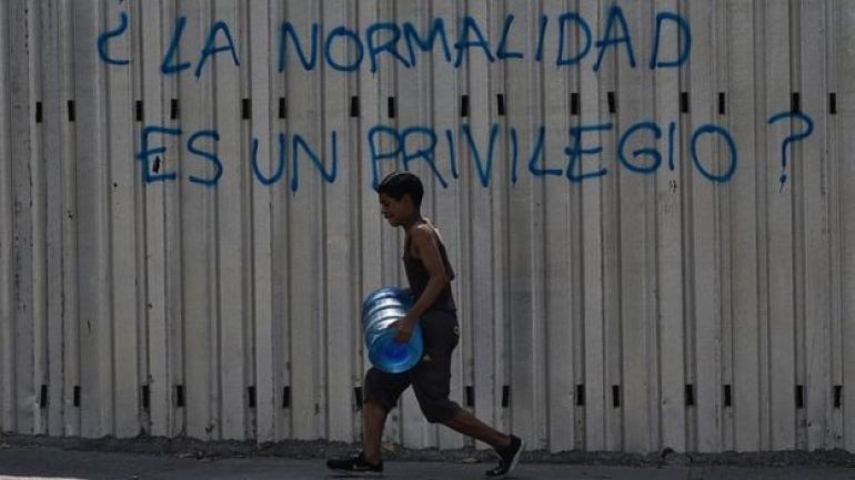 Un joven carga un bidón de agua por una calle de Caracas.
