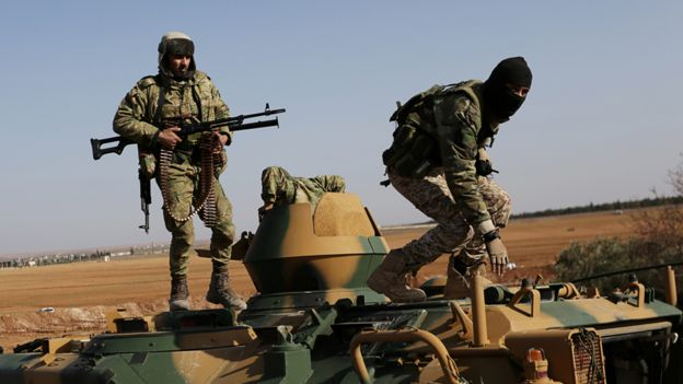 Rebel fighters stand with their weapons on a military vehicle as they head towards the northern Syrian town of al-Bab