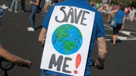 """Homem com um cartaz com um desenho da Terra escrito """"save me"""" (me salve, em inglês)"""