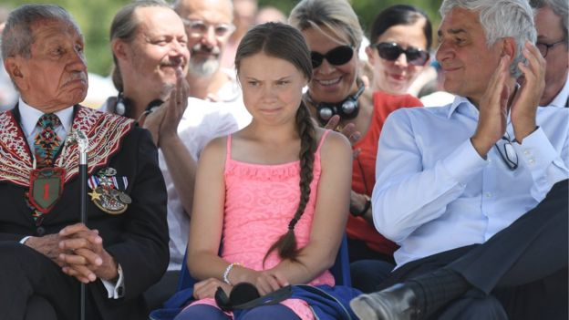 Greta Thunberg sitting in a crowd of people