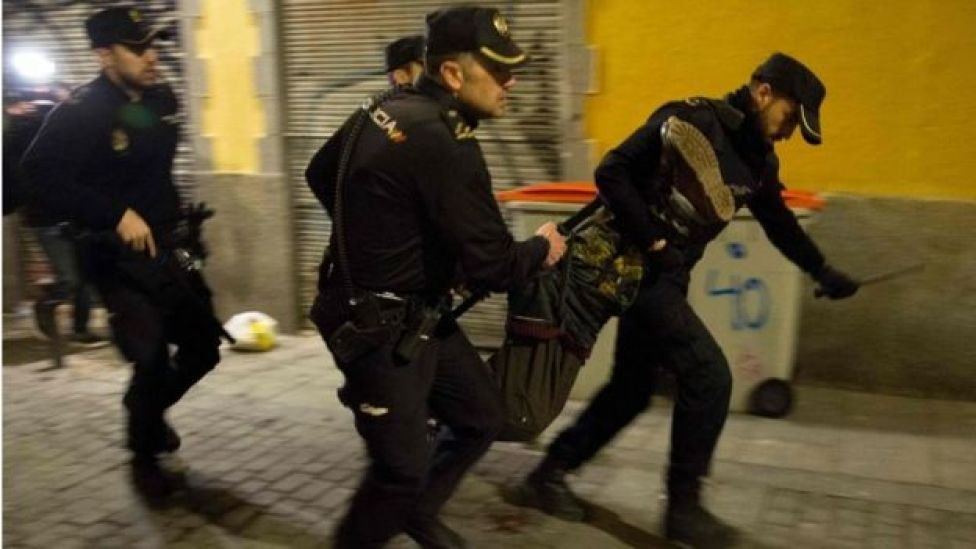 Spanish police run through the streets carrying a protester who fell down during a police charge in the Lavapies district