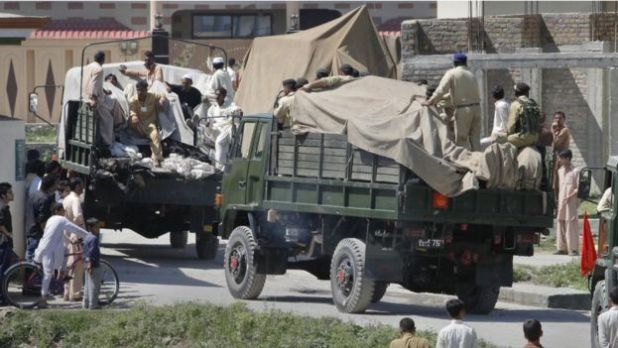 Soldiers and residents stand over covered debris as it is moved out by military vehicles from the compound within which al Qaeda leader Osama bin Laden was killed, in Abbottabad in this May 2, 2011
