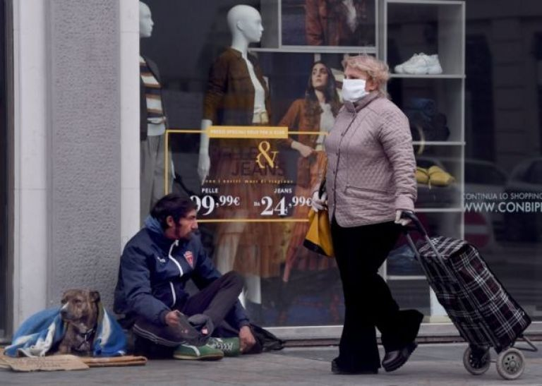 Mulher usando máscara passa por morador de rua em Milão, em 25 de março de 2020