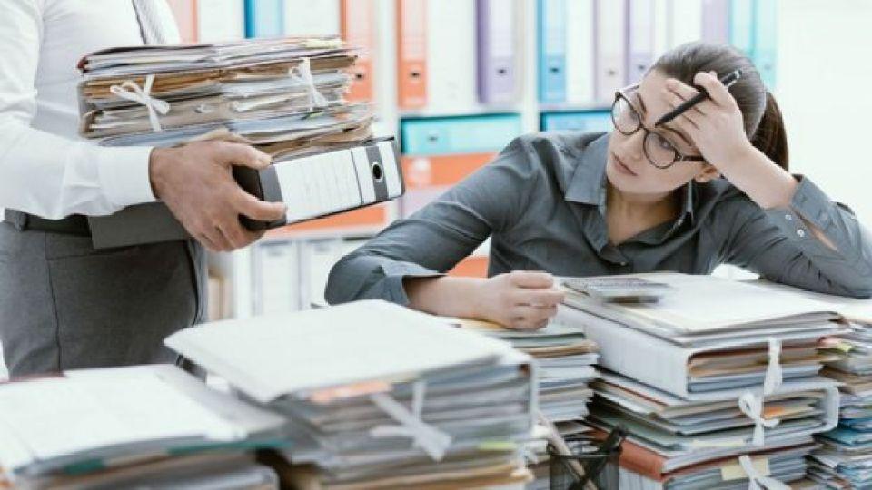Mujer en su escritorio lleno de papeles