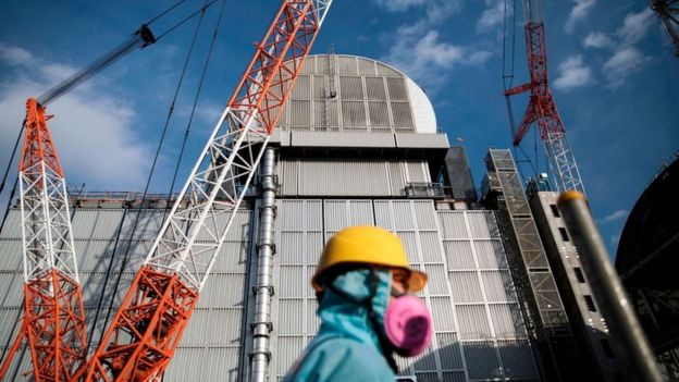 An employee of Tokyo Electric Power Company (TEPCO) walks past the company's reactor number 3 at Fukushima Dai-ichi nuclear power plant