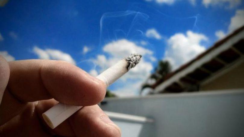 Mão segura um cigarro