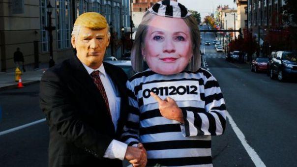 Dos personas disfrazadas de Trump de traje y de Hillary Clinton de presidiaria.