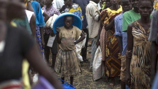 طابور من أشخاص سود البشرة ينتظرون لتلقي مساعدات