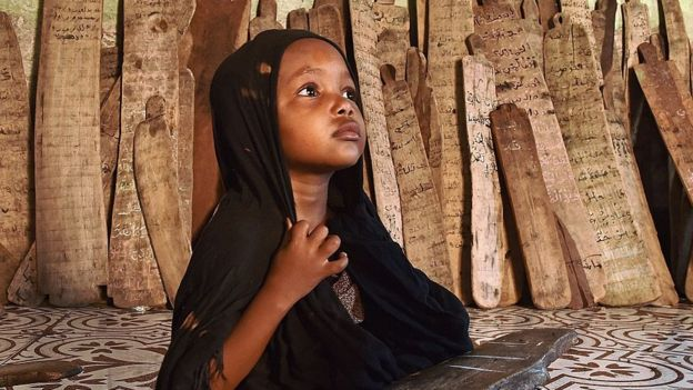 A girl in a madrassa holds a wooden board with verses of the koran written on it in Mogadishu, Somalia - 2015