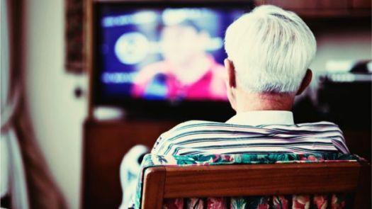 Idoso assistindo à TV
