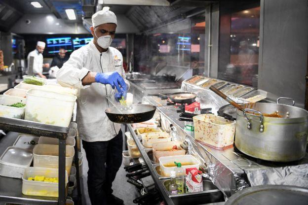 Os funcionários da cozinha do restaurante Kebabish Grill, em Glasgow, usam máscaras enquanto preparam a comida.