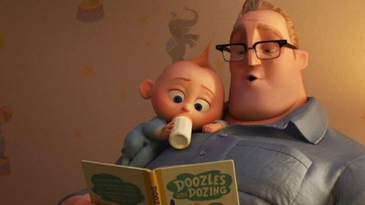 """En una foto de una escena de """"Los Increíbles 2"""" el padre lee un cuento a su hijo pequeño."""