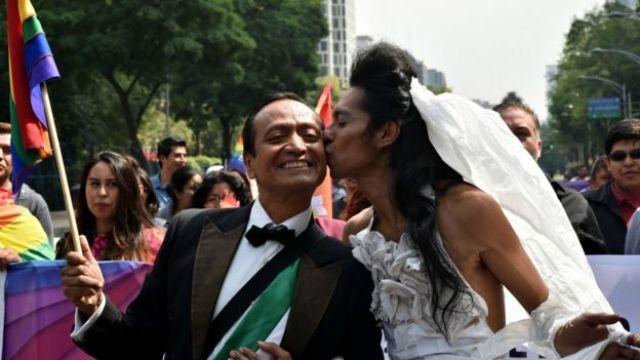 Desfile de una marcha gay en la que representan una boda de dos hombres, uno vestido de novia.