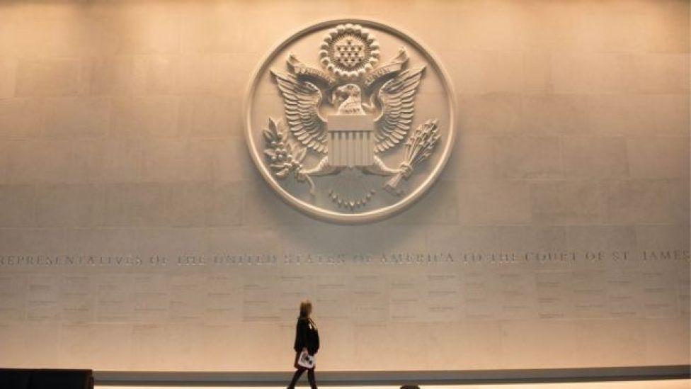 Mujer caminando en la embajada de Estados Unidos en Londres, Reino Unido.