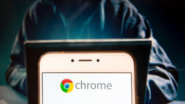 Pantalla de celular con el logo de Google Chrome y un hacker manejando una computadora.