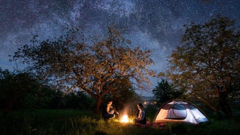 Un couple de campeurs, assis près d'un feu de camp, avec un ciel étoilé au-dessus d'eux.