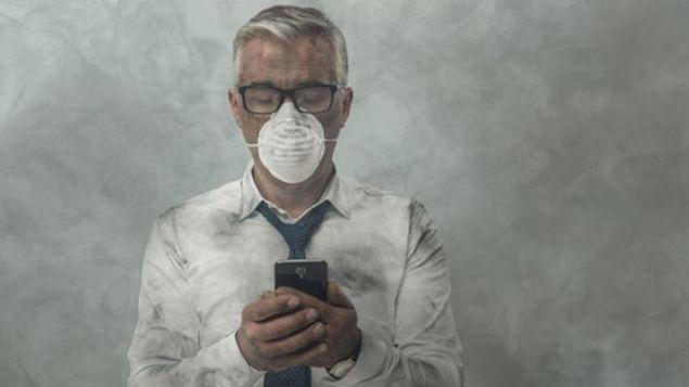 Homem com mascara e ar poluido em volta