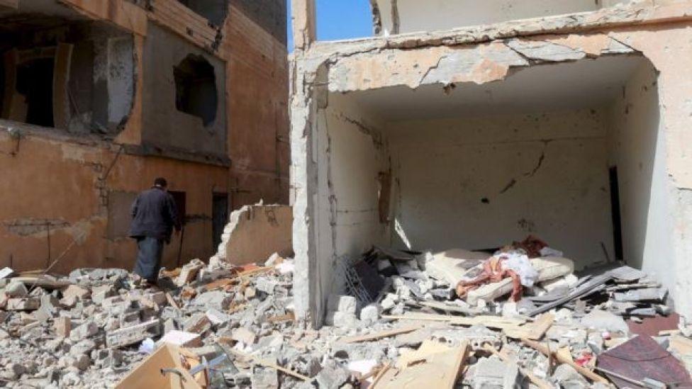 A man walks between debris following clashes in Libya
